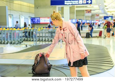 Baggage reclaimed at the airport. Elegant caucasian woman taking her backpack off the carousel baggage. Business woman picking up suitcase from conveyor belt at airport. Blurred backgorund.