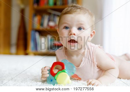 Cute happy smiling baby playing with colorful rattle toys. New born child, little girl looking at the camera and crawling. Family, new life, childhood, beginning concept. Baby learning grab