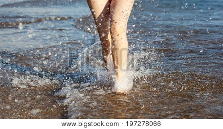 Legs of a pretty girl in red swimsuit walking in a sea