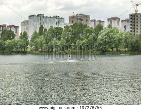 Girl is engaged in wakeboarding on the background of construction