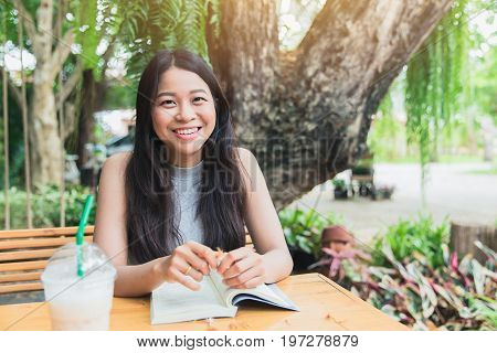 Happy Relax Times With Reading Book, Asian Women Thai Teen Smile With Book In Garden With Coffee Sho