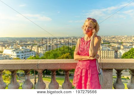 Parisian views from terrace of Sacre Coeur Cathedral, Paris, France. Businesswoman talking on smartphone. Happy woman using mobile phone app for conversation from Sacred Heart viewpoint. Sunny day.