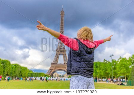 Happy tourist woman with open arms looking Tour Eiffel, icon of Paris. Caucasian lifestyle traveler enjoing at Eiffel Tower from Champ de Mars garden. Freedom and travel concept in European Capitals.