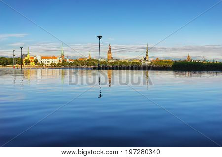 The capital of Latvia is the ancient city of Riga on the Daugava river with reflection in the water on a summer sunny day