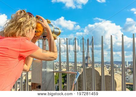 Caucasian lifestyle traveler looking skyline of Paris with tourist binocular from top of Arc de Triomphe. Blonde tourist woman looking Tour Eiffel. Landmark in Paris, France, Europe.