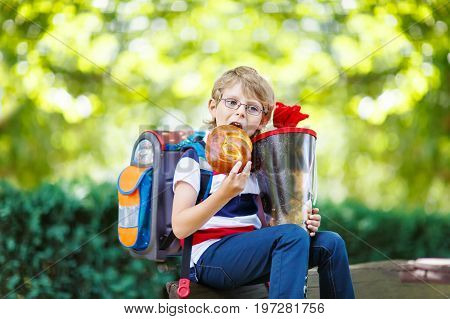 Happy little kid boy with glasses and backpack or satchel on his first day to school . Child outdoors on warm sunny day, Back to school concept. Kid with traditional schoolbag in German Schultuete