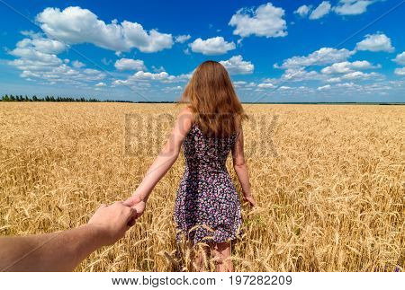Follow me. Beautiful young brunette woman holding man hand in wheat field with cloudy blue sky background free space. Couple walking hand in hand in wheat field. Travel and journey concept