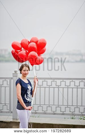 Portrait Of A Gorgeous Beautiful Bridesmaid Clothed Casually Holding Heart-shaped Red Balloons Next