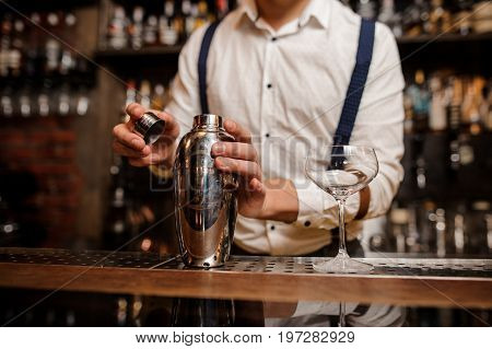 no face barman in white shirt is making a cocktail