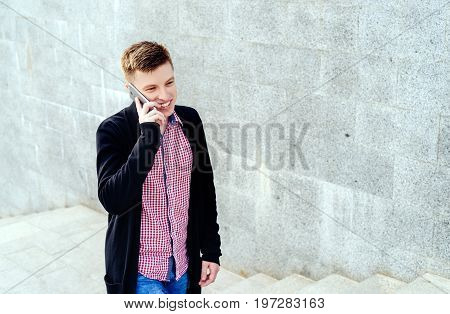 Stylish young man in plaid shirt and jeans walking up stairs and talking on cell phone full body. Student with smartphone walking up stairs free space