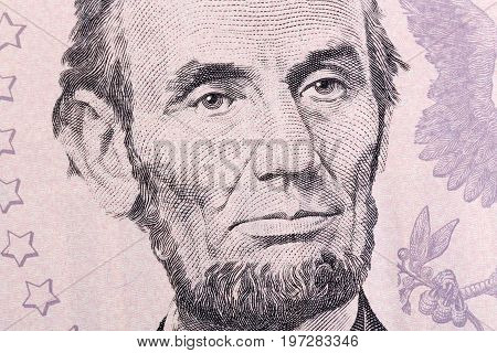 Macro portrait of Abraham Lincoln on five U.S. dollar bill. High resolution photo.