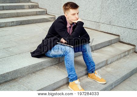 Sad pensive young man in jacket and jeans with hand on chin sitting on stairs with laptop computer outdoors free space. Technology and communication concept