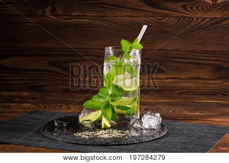 A close-up of a fresh mojito beverage with fresh slices of lime on a dark brown wooden background. Peppermint leaves, lime slices and a glass of exotic mojito. Alcoholic summer beverages.