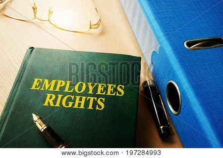 Book with name Employees Rights on an office table.