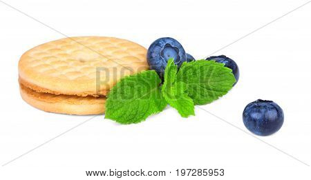 An oatmeal cookie with ripe blueberries and green peppermint leaves isolated over the white background. Healthful and tasteful snacks full of nutrients. Baked desserts and summer fruits.