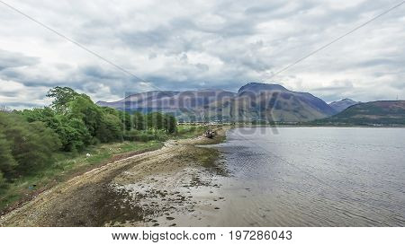 Aerial view of the abandoned ship wreck in Fort William with Ben Nevis in the background, Scotland, United Kingdom