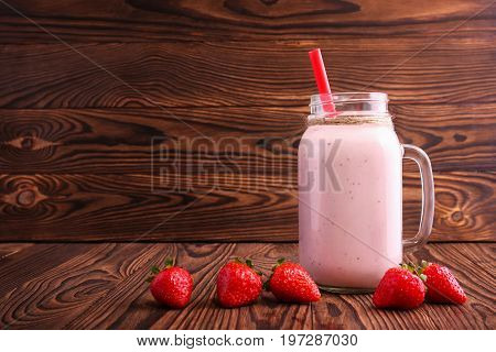 A transparent mason jar full of a pink bubbled smoothie. A mason jar of organic fruity beverage and red ripe strawberries on a bright wooden background. Vegetarian dieting concept. Copy space.
