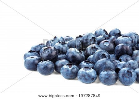 A close-up picture of a group of blueberries isolated on a white background. Tasty and ripe saturated blueberries. Refreshing and organic blueberries for summer yogurts and fruit salads.