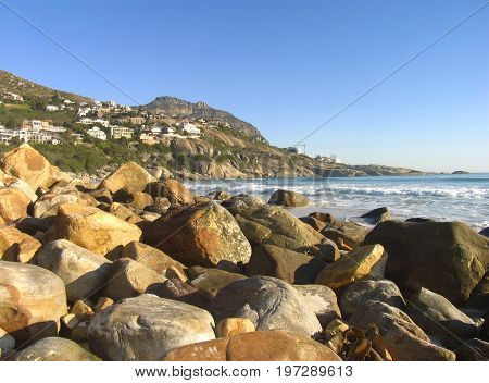 FROM CAPE TOWN, SOUTH AFRICA, LLUNDUDNO, WITH HUGE ROCKS IN THE FORE GROUND AND MOUNTAINS IN THE BACK GROUND