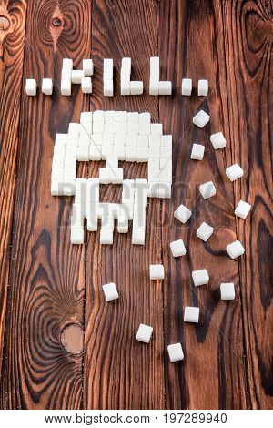 A gross symbol of a skull made of white sugar pieces on a wooden background. Sweet sugar cubes on a dark brown table. Unhealthy refined sugar forming a word