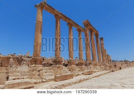 The ancient Roman city in Jerach Jordan Colonnaded Street summer time blue sky background.