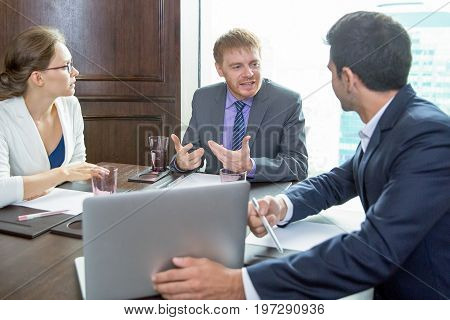 Closeup of three serious adult business partners sitting at table, using laptop computer and discussing issues in meeting room with big window and building view outside in background