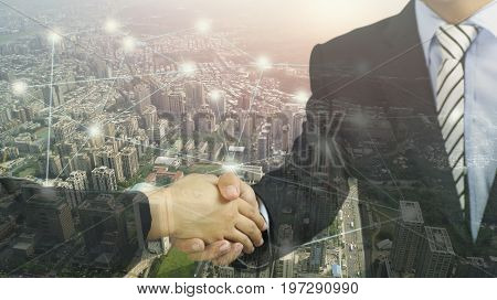 double exposure city and shaking hand concept in connection and success in bussiness