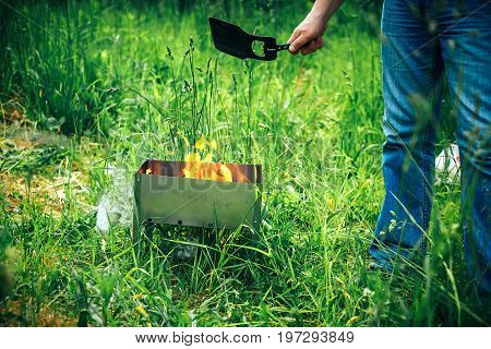 flame grilled and wood burning in fire on BBQ party. family barbecue party in outdoor or home garden. A man blows coals in a fire with plastic shovel for the fire