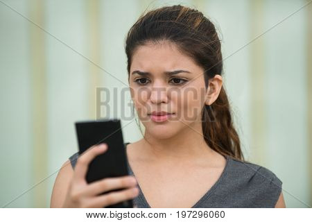 Portrait of young Caucasian woman holding cellphone, reading message and frowning