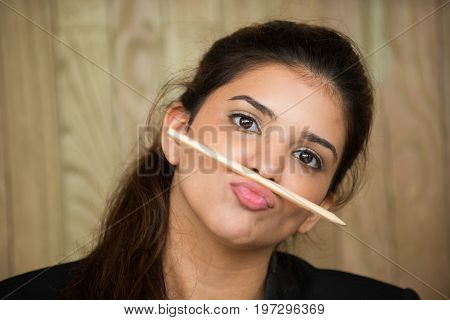 Close-up of face of funny young Caucasian woman putting pencil between lip and nose and grimacing