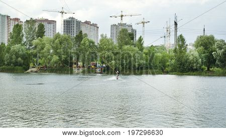 Man is engaged in wakeboarding on the lake on the background of city construction