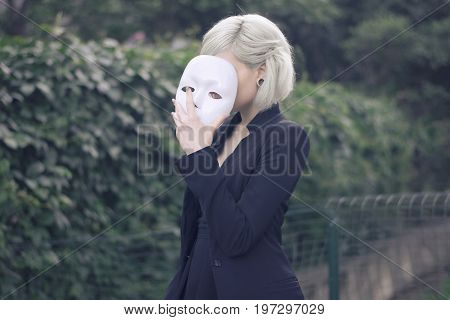 Young blond girl taking off a mask. to be someone else concept. outdoors