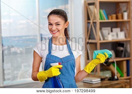 Studio shot of housekeeper. Beautiful woman cleaning office. Woman wearing gloves, smiling and holding bottle with disinfectant