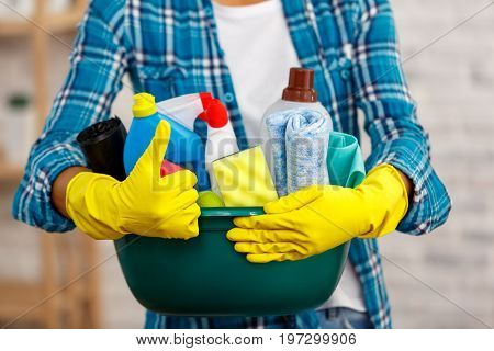 Studio shot of housekeeper while cleaning room. Woman wearing gloves, showing thumb up and holding bowl full of bottles with disinfectant