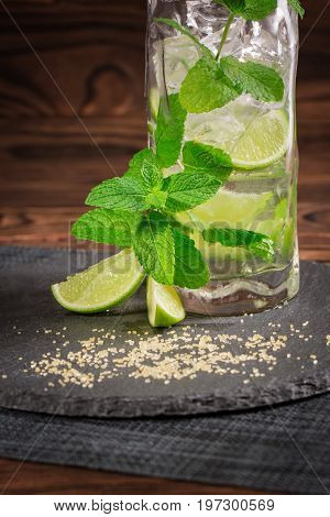 Close-up of a tasty organic beverage on a black desk with fresh lime segments, ice cubes and mint twigs on a wooden background. Beverages for summer parties. Alcoholic cocktails. Copy space.