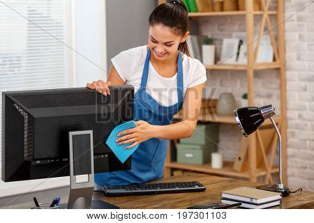 Studio shot of housekeeper. Beautiful woman cleaning computer at office and smiling