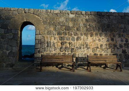 Vintage Color Tone Style Of Wooden Bench Antique With Sunrise By Old City Stone Wall