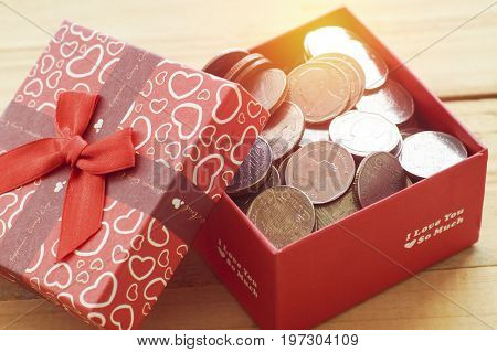money coins in present and gift box on wood table