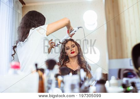 Hair stylist making ringlets to brunette woman. Hairdresser working with beautiful woman hair in hairdressing salon. poster