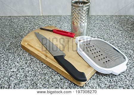 Useful elements in the kitchen like blade wood board grater and peeler.
