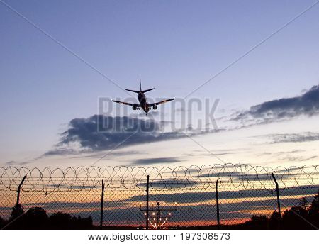 Skyline of passangers airplane landing at sunset