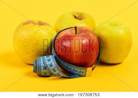 Tape For Measuring And Colorful Apples On Yellow Background