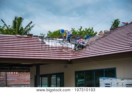 Workers are tiling new roof tiles on high.