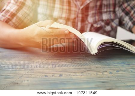 hand of people student opening and reading text book on wood table with copy space in library concept as education attempt and make effort to win intend to improve knowledge for future life