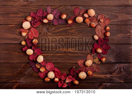 Flat lay frame in the form of a heart of autumn crimson leaves hazelnuts and walnuts on a dark wooden background. Selective focus.