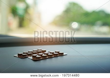 Brown blisters pack of pills on car console expose directly to sunlight.