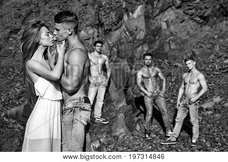 macho men with muscular sexy body and six packs on torso in jeans and pretty woman in dress sunny outdoor on natural background black and white