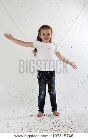 Cute little girl bare feet throwing confetti