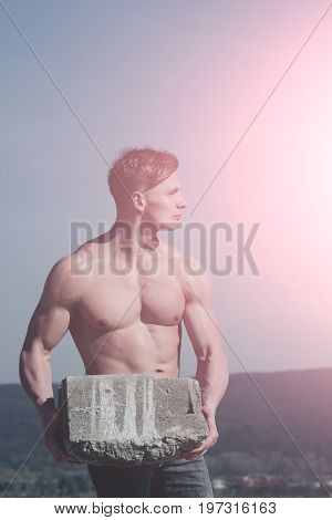 Man builder with muscular body. Athletic bodybuilder as hercules. Gladiator or atlant. Sport and workout. Adam hold bog stone.