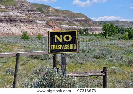 No trespassing sign on fence with desert in background